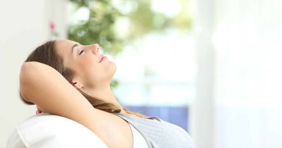Woman Relaxing in Air Conditioned Living Room